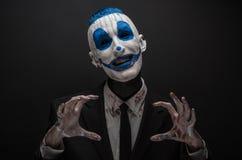 Payaso terrible y tema de Halloween: Payaso azul loco en el traje negro aislado en un fondo oscuro en el estudio Foto de archivo libre de regalías