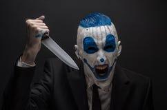 Payaso terrible y tema de Halloween: Payaso azul loco en un traje negro con un cuchillo en su mano aislada en un fondo oscuro en Fotografía de archivo