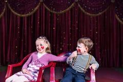 Payasos jovenes que se sientan y que ríen en etapa Foto de archivo