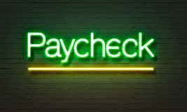 Paycheck neon sign on brick wall background. Royalty Free Stock Image
