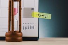 PAYDAY λέξης που γράφεται σε κίτρινα κολλώδη χαρτί και το ημερολόγιο πέρα στοκ φωτογραφίες