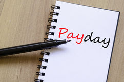 Payday Concept. White notepad and ink pen on the wooden desk Payday Concept Royalty Free Stock Images