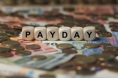Payday - cube with letters, money sector terms - sign with wooden cubes. Series of cube with letters from money sector Royalty Free Stock Photo