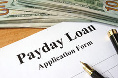 Payday loan form. Payday loan form on a wooden table Stock Image