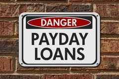 Payday Loans Danger Sign. A white danger hanging sign with text Payday Loans on a brick building Stock Photos