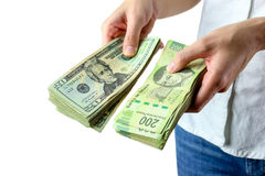 Payday. A Woman giving some mexican pesos and dollars bills Stock Image