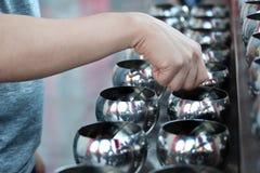 Payez les pièces de monnaie dans des 109 cuvettes de moine de manière bouddhiste de culte Photographie stock libre de droits