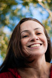 Paying attention. Beautiful latin middle aged woman in the park smiling stock photo