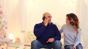 Paying attention of stately husband to sweet wife and putting off all affairs. Loving couple sitting on bed in bedroom. Modern confident male speaks on phone stock video footage