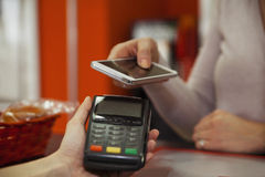 Paying A Bill. Paying  A Bill Through Smart Phone Using NFC Technology Stock Photo