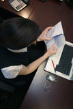 Paying Bills. Caucasian businesswoman paying bills while seated at her desk Stock Photo