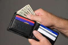 Paying bills. Dishing out cash from a leather wallet to pay bills Royalty Free Stock Image