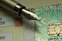 Paying bills by credit card. A closeup of a bill or invoice, credit card and a fountain pen Royalty Free Stock Images