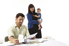 Paying bills family finances. Modern young American family stressed about paying bills wondering how to make ends meet. Asian husband paying bills Royalty Free Stock Photography