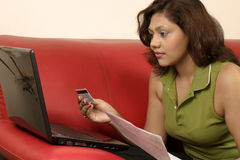 Paying bills online. Young indian woman with credit card and laptop paying bill online Stock Photography