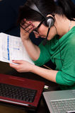 Paying bills online. Woman paying her bills online, troubled by the amount to pay Stock Photos