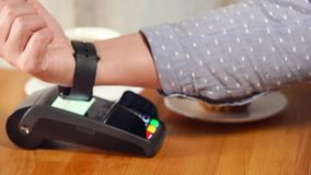 Paying in cafe with NFC technology on smart watch stock video