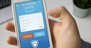 Paying for car insurance bill using smartphone application stock video