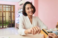 Paying with card. Beautiful Vietnamese young women paying with credit card in spa salon stock images