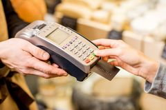 Paying with card in the food store. Woman paying with card in the food store. Close-up view on the terminale and card Royalty Free Stock Photo