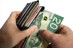 Paying Cash with Canadian Currency. The action of pulling canadian money out of a wallet Royalty Free Stock Image