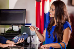 Paying at a cash register. Cute young woman paying with a credit card in a cash register and smiling Stock Images