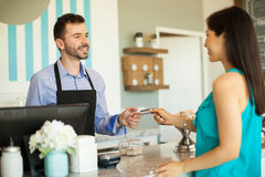 Paying at a cash register. Young brunette paying with a credit card at the cash register in a cake shop stock photography