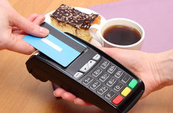 Paying with contactless credit card for cheesecake and coffee in cafe, finance concept. Use payment terminal with contactless credit card with NFC technology for stock photography