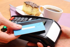 Paying with contactless credit card for cheesecake and coffee in cafe, finance concept Stock Images