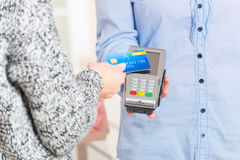 Paying with contactless credit or debit card. Hand holding contactless credit or debit card over wireless payment terminal at shop royalty free stock photos