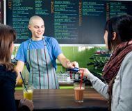 Paying with credit card. Bartender receiving credit card of customer for payment in cafe Stock Images