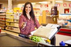 Paying with a credit card. Beautiful young woman at the cash register of a supermarket paying with a credit card and smiling Stock Photos