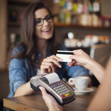 Paying by credit card. Happy woman paying for cafe by credit card Stock Photos