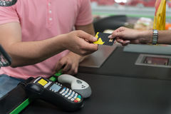 Paying With Credit Card for Purchases. Close Up Woman Paying Groceries at Supermarket Checkout With Card Stock Images