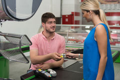 Paying With Credit Card for Purchases. Smiling Woman Paying Groceries at Supermarket Checkout With Card Royalty Free Stock Photo