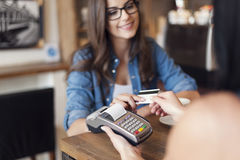 Paying by credit card. Smiling woman paying for coffee by credit card Stock Photography