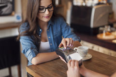 Paying by credit card. Young woman paying for cafe by credit card reader Royalty Free Stock Images