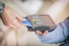 Paying with credit or debit card. In wireless payment terminal at shop Royalty Free Stock Photo