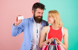 Paying while dating. Couple with luxury bags in shopping mall. Man bearded hipster hold credit card and girl enjoy. Shopping. Ask men to purchase lots presents royalty free stock photo