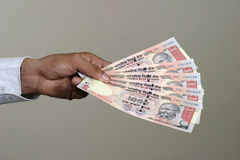 Paying in indian rupee. Close up of a  hand paying in indian currency with thousand rupee notes Stock Photo
