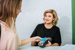 Dark-haired woman wearing blouse paying for her massage by card stock photos