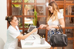 Paying for a massage at the spa. Cute young women using a credit card to pay for a massage at a health and beauty spa and smiling Stock Photo