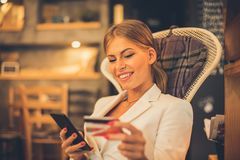 Paying online with her credit card. Smiling young woman paying online with her credit card. Focus is on background royalty free stock image