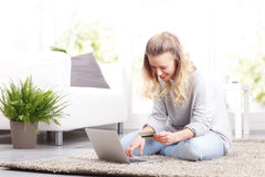 Paying online. Portrait of young woman sitting at home in front of laptop. Smiling female paying bills online while typing on keyboard and holding in hand a bank Royalty Free Stock Images