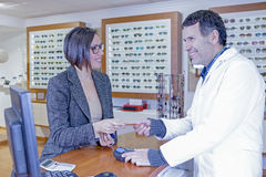 Paying at optical store. Smiling young women is paying with a credit card to a male optometrist at the optical shop - focus on the women eye Royalty Free Stock Photo