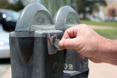 Paying the parking meter. A man's hand inserting a quarter into a double-headed parking meter Stock Image