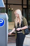 Paying at a parking meter. Young woman model paying interfacing with a parking meter Royalty Free Stock Images