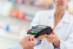Paying in the Pharmacy. Customer Paying Through Credit Card in Pharmacy Royalty Free Stock Photography