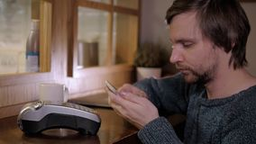 Paying with smartphone. Handsome man making payment transaction with his mobile phone to waiter in modern cafe. Paying with smartphone. Closeup of man making stock footage