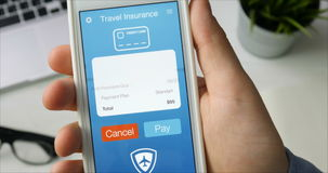 Paying for travel insurance using smartphone app sitting at the desk. Paying for health insurance using smartphone app sitting at the desk Stock footage stock footage